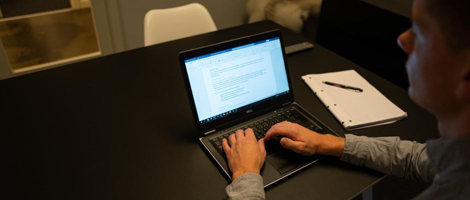 Aske sidder og skriver på PC. Han sidder i et mørkere lokale ved et skrivebord.