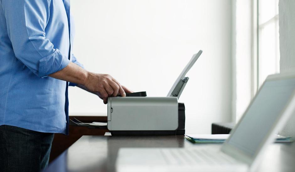 En mand står og printer et stykke papir ud.